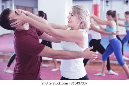 Sporty glad cheerful positive mature woman with her instructor are training self-defence moves in gym.