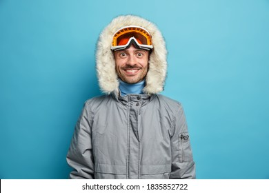 Sporty glad man enjoys winter sport recreation smiles gladfully wears ski goggles and grey jacket isolated on blue. Holidays tour recreation and traveling concept. Snowboarder leads active lifestyle - Shutterstock ID 1835852722