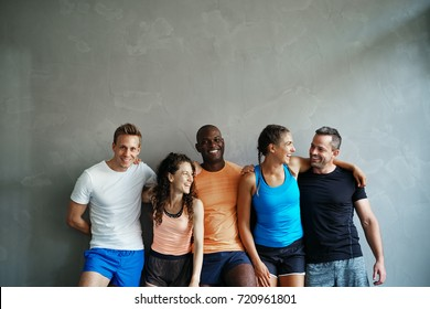 Sporty group of young friends in sportswear laughing while standing arm in arm together in a gym after a workout