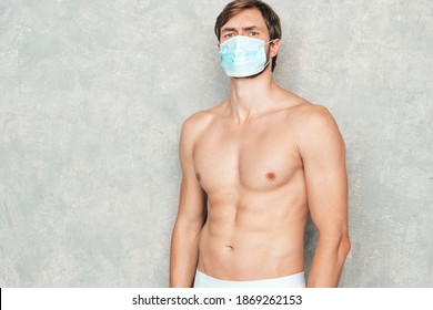 Sporty handsome strong man. Healthy athletic fitness model posing near gray wall in white underwear. Confident sexy fashion male with naked nude torso. Wearing protective mask for corona virus
