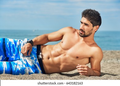 Sporty handsome young man with naked torso lying on the beach. Sea background.