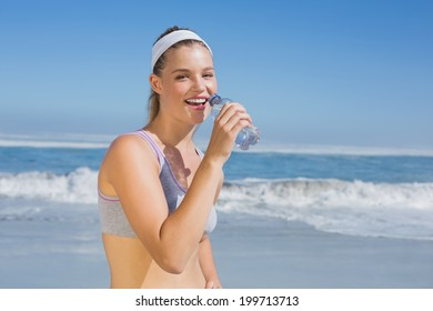 Sporty happy blonde drinking water on the beach on a sunny day