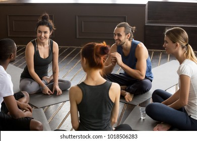 Sporty happy multi-ethnic people sitting on mats after group meditation relaxing talking about healthy life motivation before training class, discussion at yoga seminar for self-improvement concept