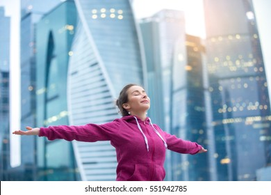 Sporty healthy model wearing pink hoody, feeling alive with arms outstretched to sky, closed eyes, enjoying bliss, fresh air, thanking for good weather, doing yoga, fitness outdoor, urban background
