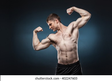 Sporty and healthy muscular man isolated on dark blue background