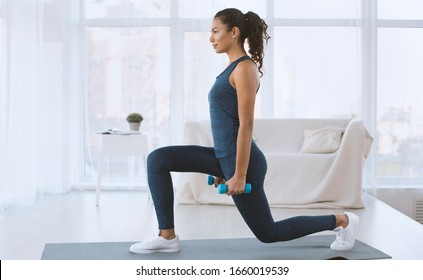 Sporty Hispanic girl doing lunges with dumbbells at home, empty space
