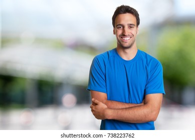 Sporty hispanic man with beard looking at camera outdoor in the summer