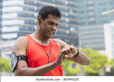 Sporty Indian man looking at his smart watch heart rate monitor. Athletic Asian man using a smart watch and listening to music with earphones.