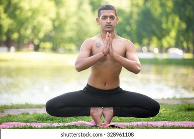 Sporty Indian young man working out on lake, doing yoga, fitness or pilates training, sitting in squat, palms in Namaste, mulabhandhasana, Root Chakra Pose easy variation, full length, front view