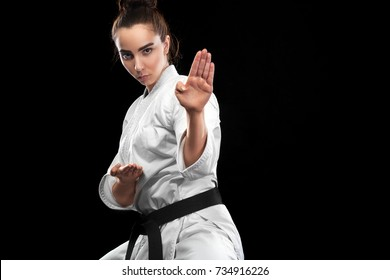 Sporty karate and taekwondo woman in white kimono with black belt on dark background. Sport concept with copy space.
