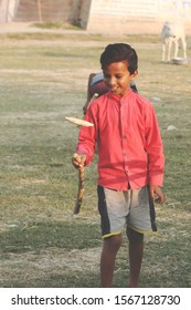 A sporty kid playing indian popular game called Gilli Danda on the ground with his friends on a sunny morning.