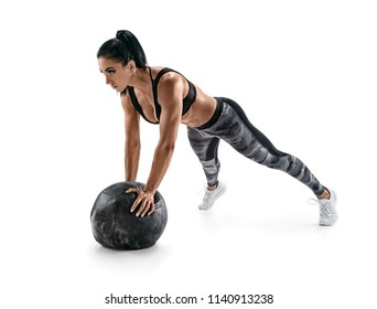 Sporty latin woman doing push ups on med ball. Photo of woman in military sportswear isolated on white background. Strength and motivation