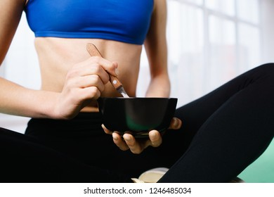 sporty lifestyle, proper nutrition, healthy ration. fit woman snacking with protein smoothie bowl after workout