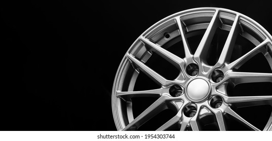 sporty lightweight alloy wheel, spokes and rim close-up on a black background, copy space