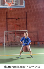 Sporty little boy playing basketball on an indoor court standing below the goal bouncing the ball and smiling at the camera