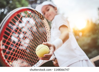 Sporty little girl preparing to serve tennis ball. Close up of beautiful yong girl holding tennis ball and racket. Child tennis player preparing to serve.