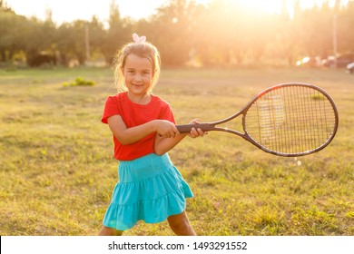 Sporty little girl preparing to serve tennis ball. Close up of beautiful yong girl holding tennis ball and racket. Child tennis player