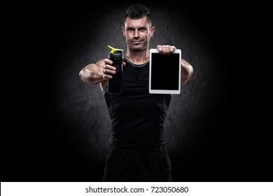 Sporty looking healthy strong muscle charismatic handsome happy smiling man bodybuilder with cool creative hairstyle in black tank top and shorts holding drinking bottle and white pad in front of him
