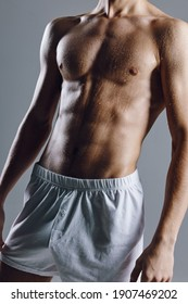sporty male bodybuilder with abs cubes on stomach gray background