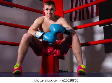 Sporty male boxer with bare chest in boxing gloves sitting near red corner of a regular boxing ring in a gym