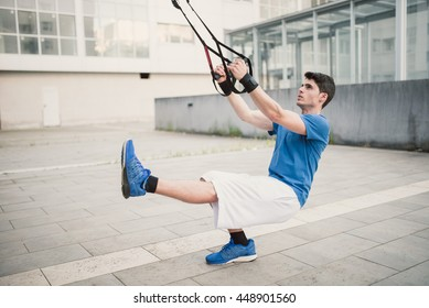 Sporty male exercising with fitness trx straps in the street