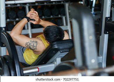 Sporty man checking heart rate when performing exercise on bench