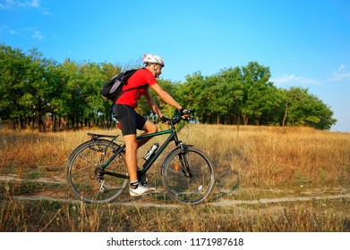 Sporty man cycling at the wild nature