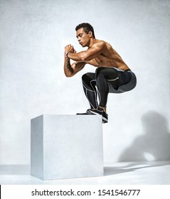 Sporty man doing box jump workout. Photo of muscular man on grey background. Strength and motivation. Full length. Side view