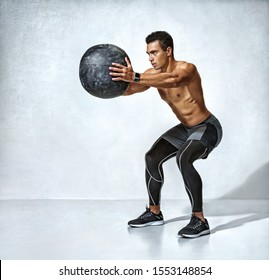 Sporty man doing squats with med ball. Photo of muscular fitness model on grey background. Fitness and healthy lifestyle concept