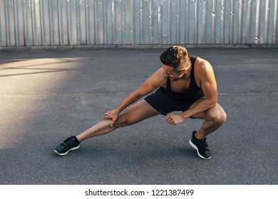 Sporty man doing warm up and stretch legs outdoor. fitness, training, healthy lifestyle