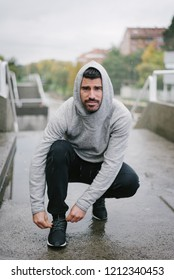 Sporty man getting ready for winter running and outdoor fitness workout under the rain. Sportsman lacing sport shoes on urban stairs.