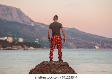 A sporty man in a gray T-shirt and bright orange camouflage stands on a rock by the sea. In the background, the setting sun and mountains. Crimea, Foros