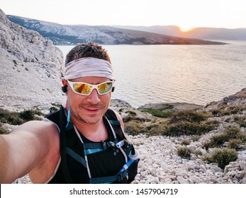 sporty man with grey hair and cool sunglasses is Trailrunning in Croatia during the sunrise and does a selfie