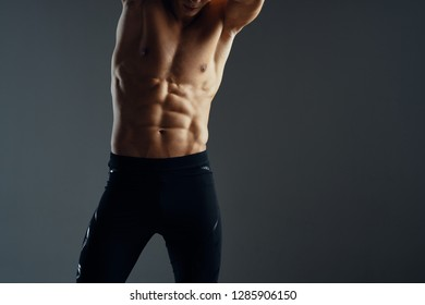 sporty man with a muscular press in black pants on a dark isolated background sport fitnes
