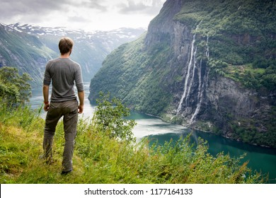 A sporty man overlooking a the Geirangerfjord and Seven Sisters waterfall in Norway