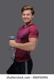 Sporty man in a red t shirt holds dumbbells.