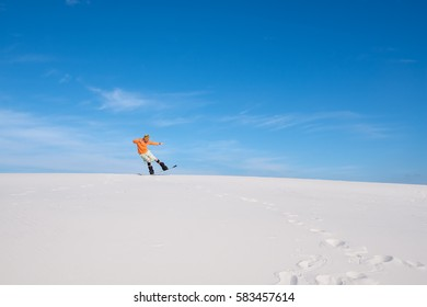 Sporty man rides on the snowboard in the sand dunes, does tricks and enjoying life. Sand boarding in the desert at sunny day. Wide angle of shooting.