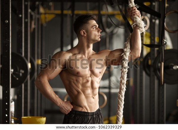 Sporty man with a rope. Photo of young man with perfect body after training. Strength and motivation