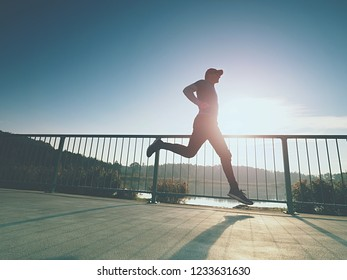 Sporty man run up the bridge . Sport and lifestyle concept - slim man running over city bridge. Runner working out outdoors