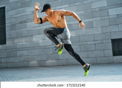 Sporty man running. Side view of active man training in the city. Dynamic movement. Sports and healthy lifestyle