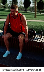 sporty man sits on a park bench in nature with dumbbells and backpack sneakers
