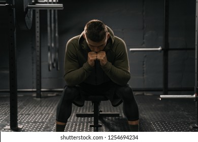 Sporty man sitting on gym bench suffering breakdown to overcome. Demotivation sport stress concept. Cross fit training.