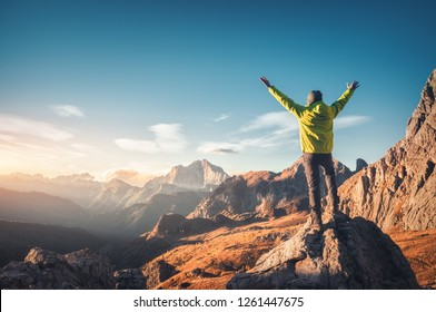 Sporty man standing on the stone with raised up arms against mountain valley at sunset. Happy young man, rocks, autumn forest and blue sky in Dolomites, Italy. Traveler hiking in alpine mountains