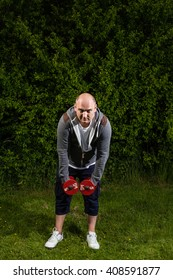 Sporty man starts exercising with 5kg dumbbells outdoors on a green meadow