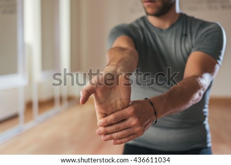 Sporty man stretching arm before gym workout. Fitness strong male athlete standing indoor warming up.