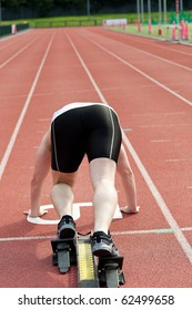 Sporty man waiting in starting block in a stadium