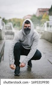 Sportlicher Mann mit Gesichtsmaske zum Schutz gegen Koronavirus und Umweltverschmutzung im Winter Laufen und Outdoor Fitness Training unter dem Regen. Sportsman schnappt Sportschuhe auf urbanen Treppen.