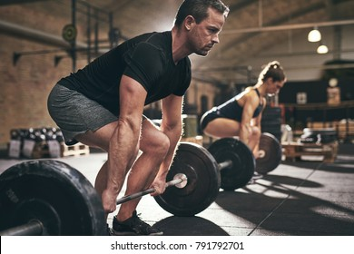 Sporty man and woman are about to lift barbells in gym. Horizontal indoors shot