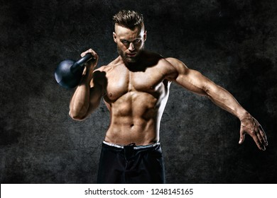 Sporty man working out with a kettlebell. Photo of man on dark background. Strength and motivation