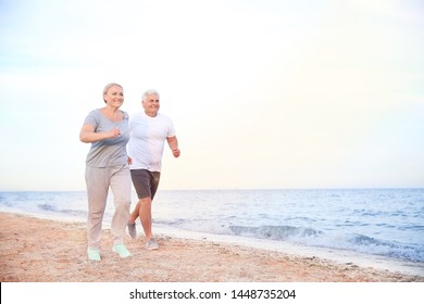 Sporty mature couple running on sea beach